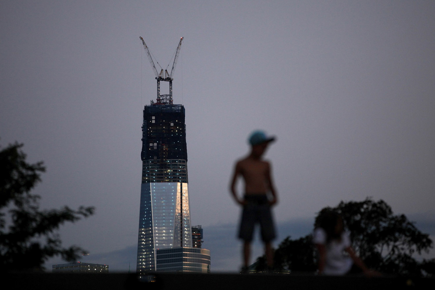 Sept. 9, 2012. One World Trade Center stands tall on the skyline of New York's Lower Manhattan as a boy stands on a pier in Hoboken, N.J.