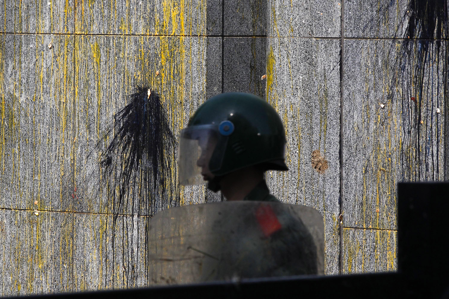 Sept. 16, 2012. A paramilitary policeman guards an entrance of the Japanese Embassy, eggs and paint splattered on its wall, in Beijing.