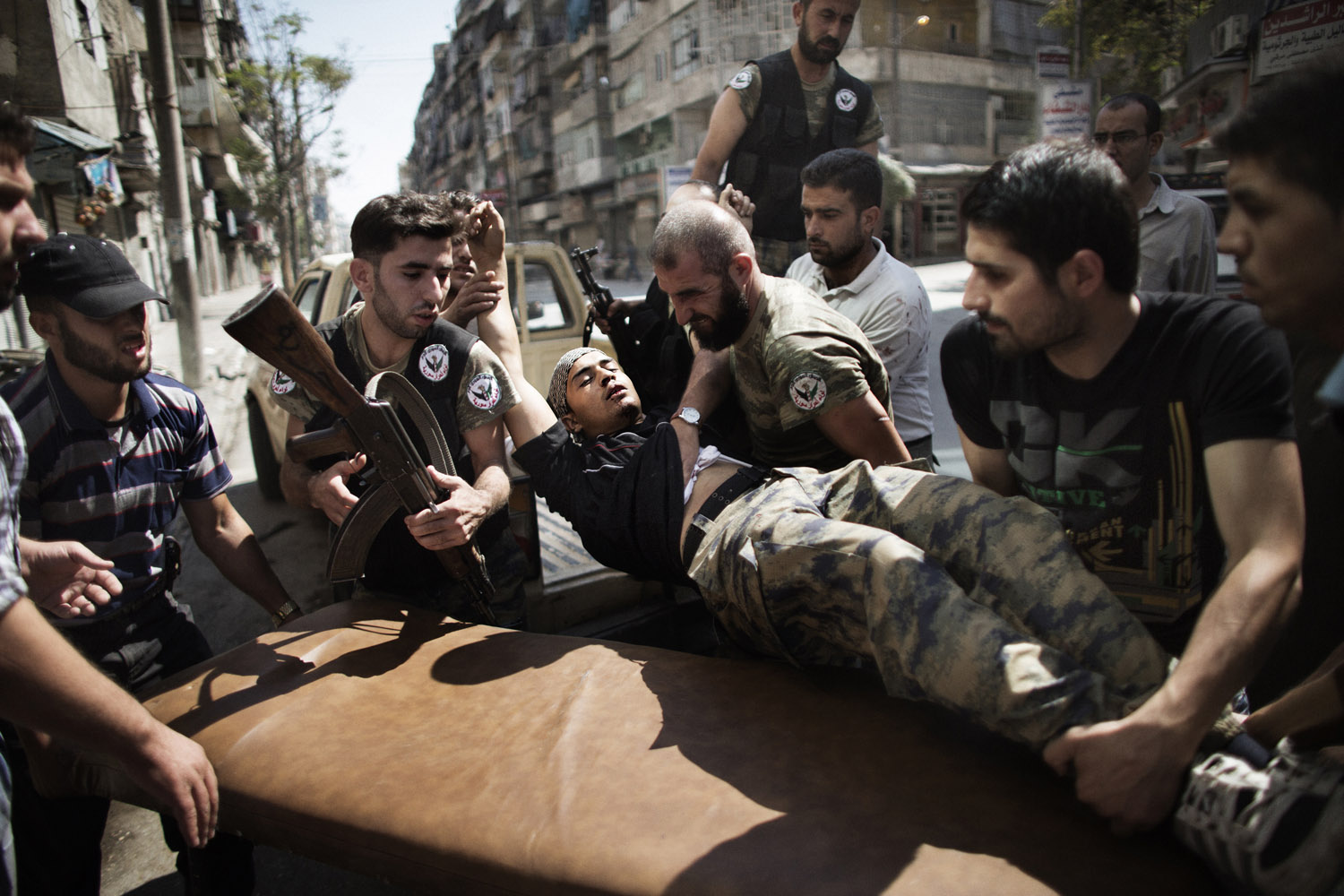 Sept. 18, 2012. Syrian rebels help a wounded comrade who survived a Syrian army strike outside a hospital in the northern city of Aleppo.