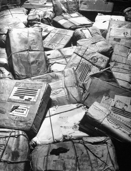 "In New York City, piles of Christmas packages meant for American servicemen who have been listed as missing or killed in action await ""return to sender"" stamp, 1944."