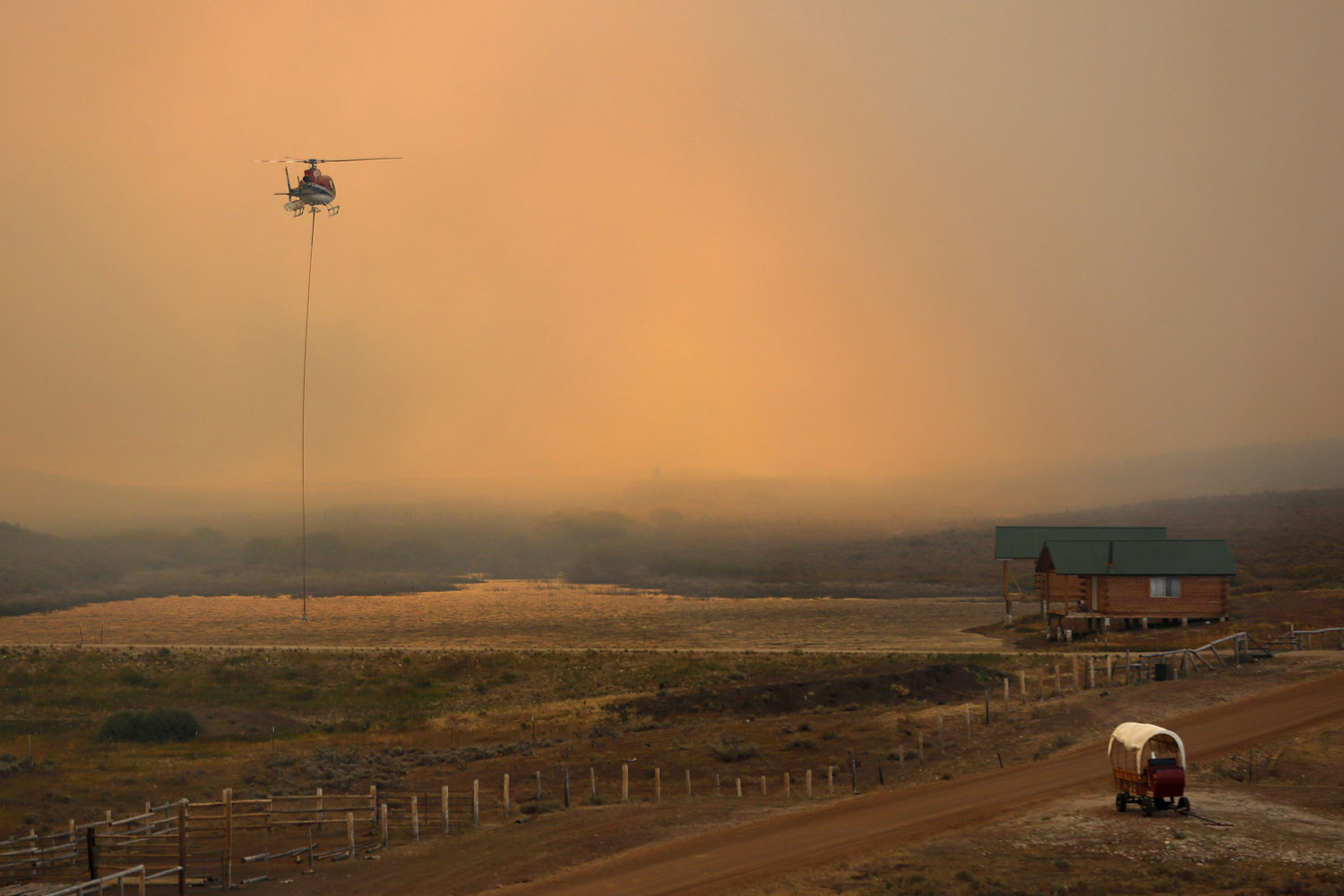 Sept. 16, 2012. A firefighting helicopter fills a bucket of water in heavy smoke as the North Merna wildfire burns in the Bridger National Forest west of the town of Pinedale in Sublette County, Wyo.