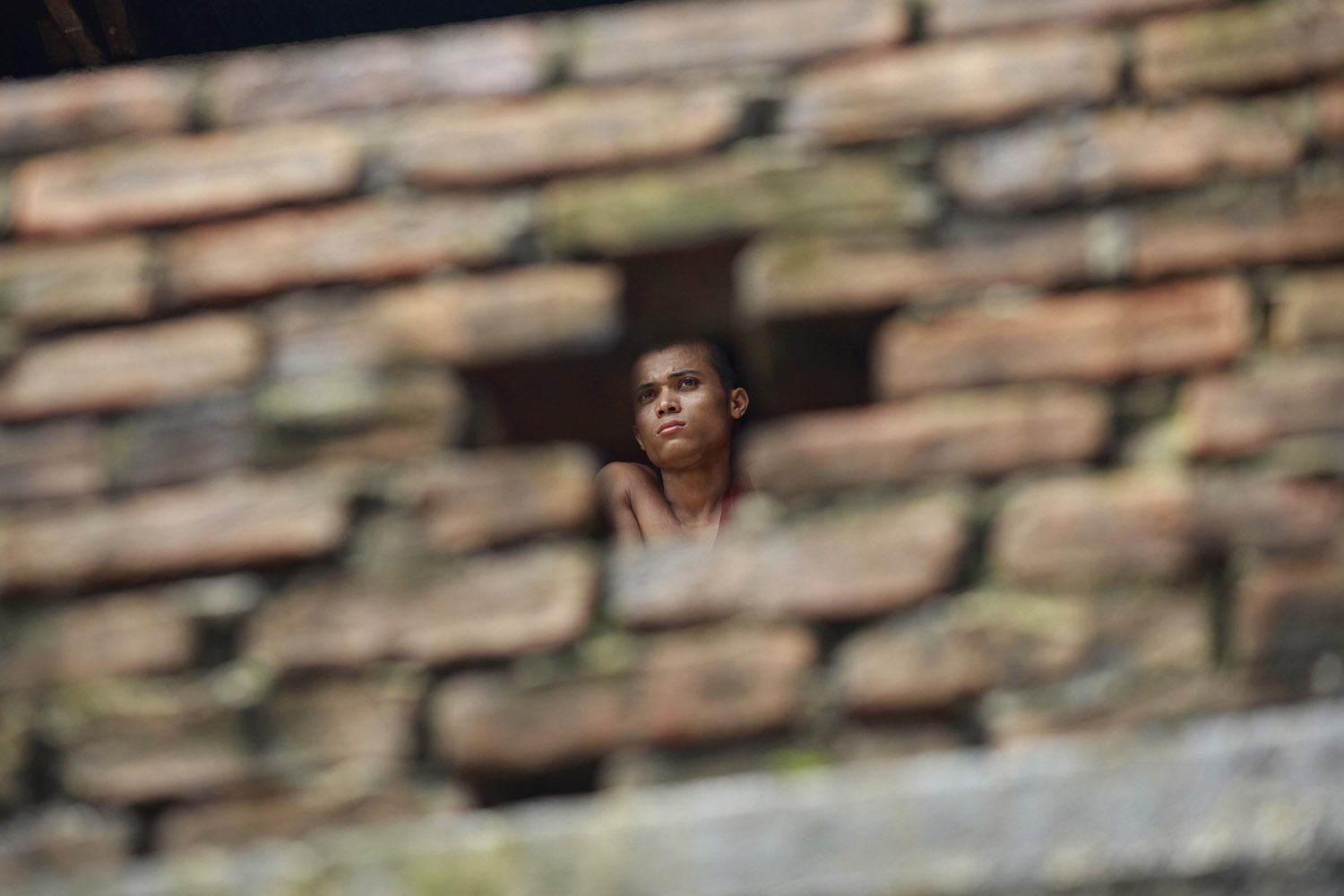 Sept. 18, 2012. A Myanmar Buddhist monk is pictured through a hole in a wall at a monastery where people gathered in the first ever rally to mark the  Saffron Revolution  in Yangon.