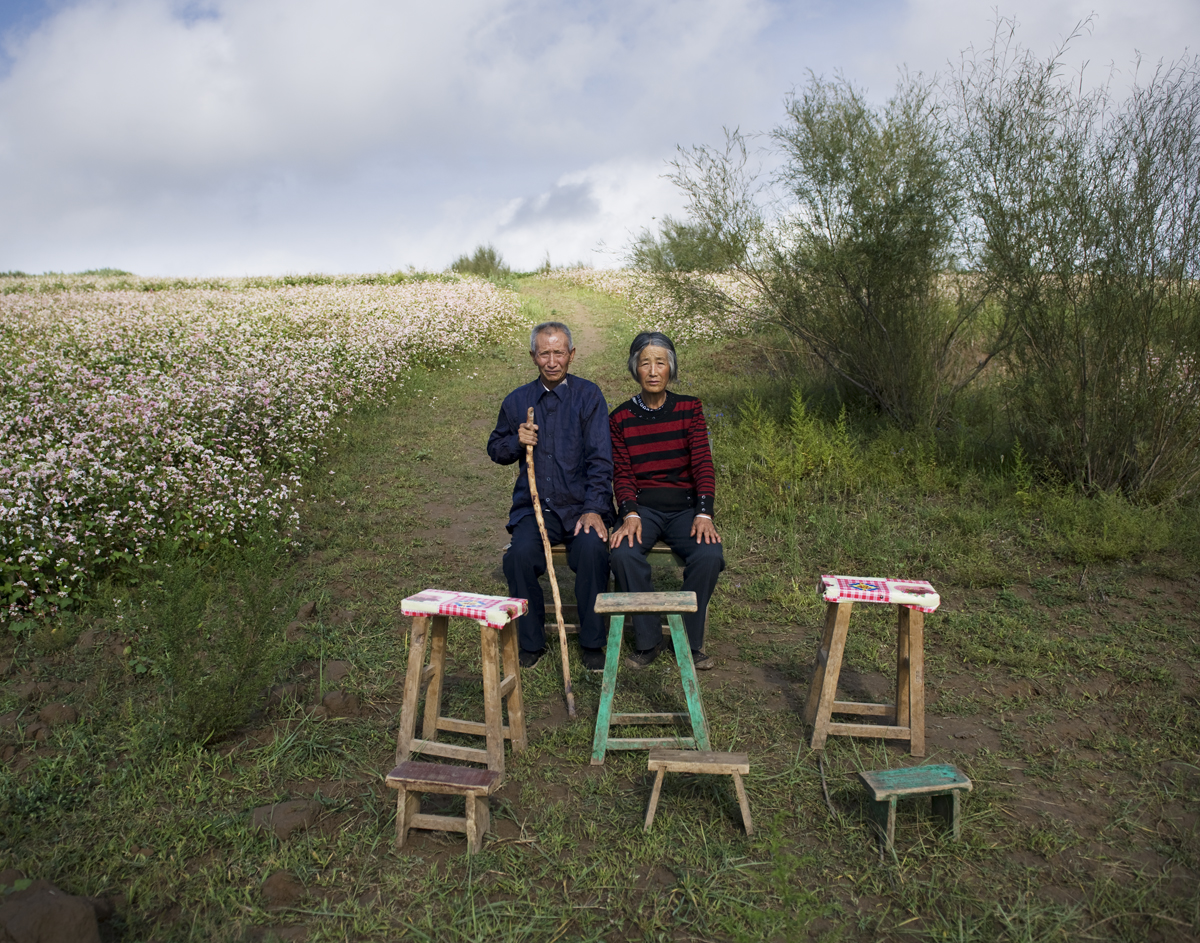Tian Yunxiu, 67 years old, and his wife Liu Dezhen sit in the farmland in Jingbian town, Shan'xi province, Aug. 24, 2011. Six family members travel to big cities to work as peasant workers.