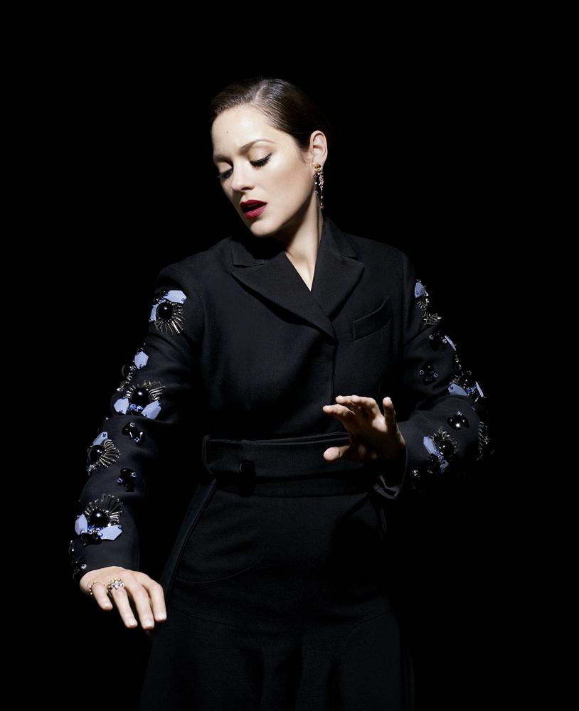 Cotillard wears Prada jacket, Andrew Gn skirt, Chanel earrings, De Beers ring and Damiani Vulcania ring.
