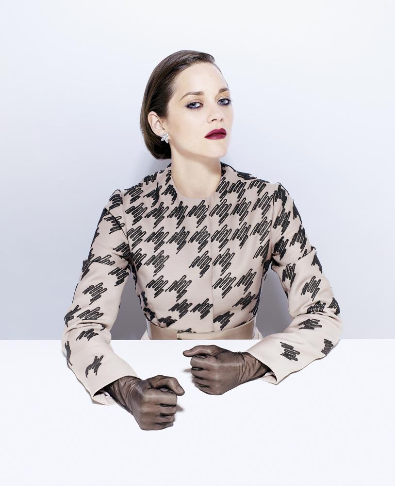 Cotillard wears Christian Dior jacket, Harry Winston earrings and LaCrasia gloves.
