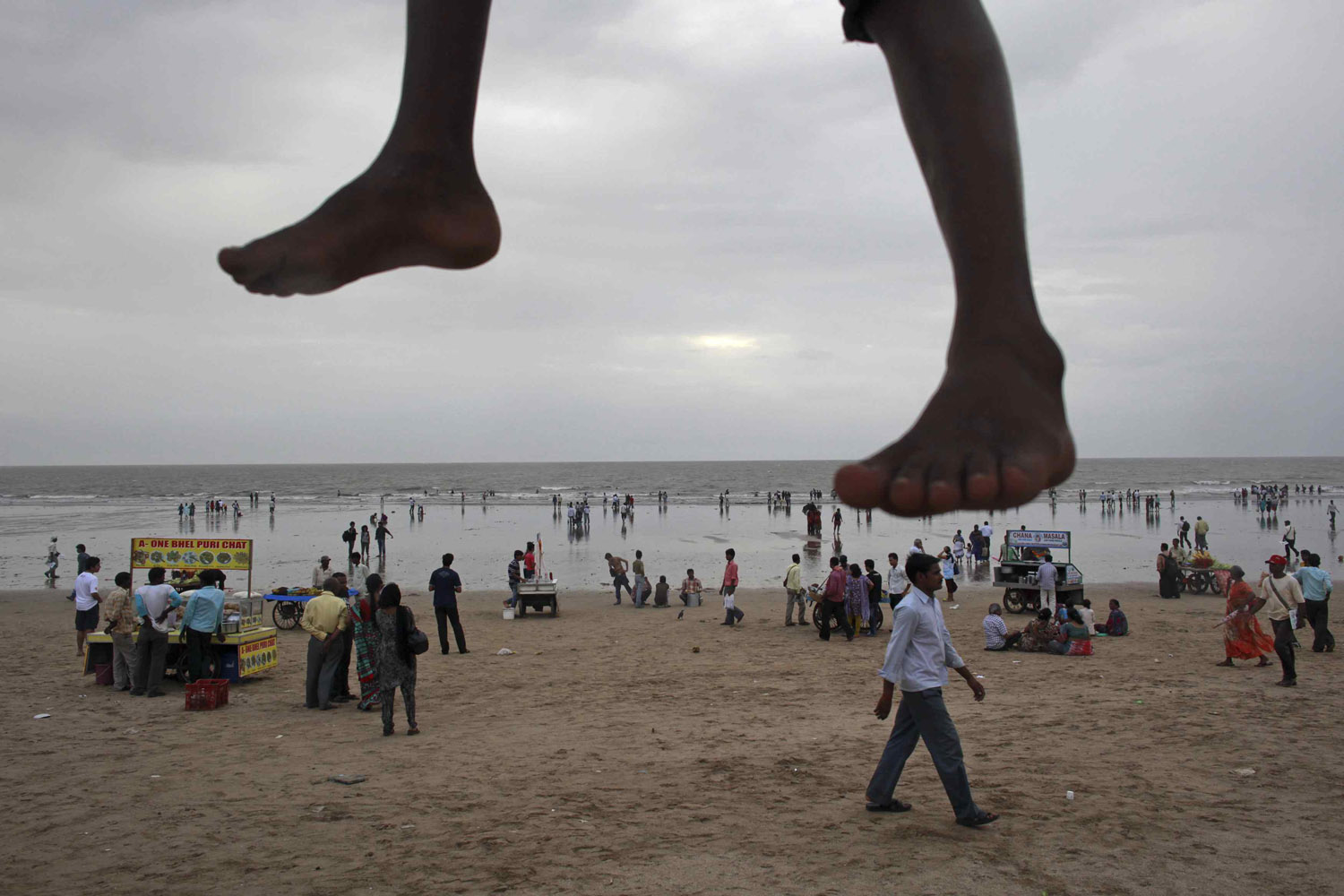 Sept. 14, 2012. A boy sits on wooden scaffolding which is used as a temporary watch tower as people stroll along Juhu beach in Mumbai.