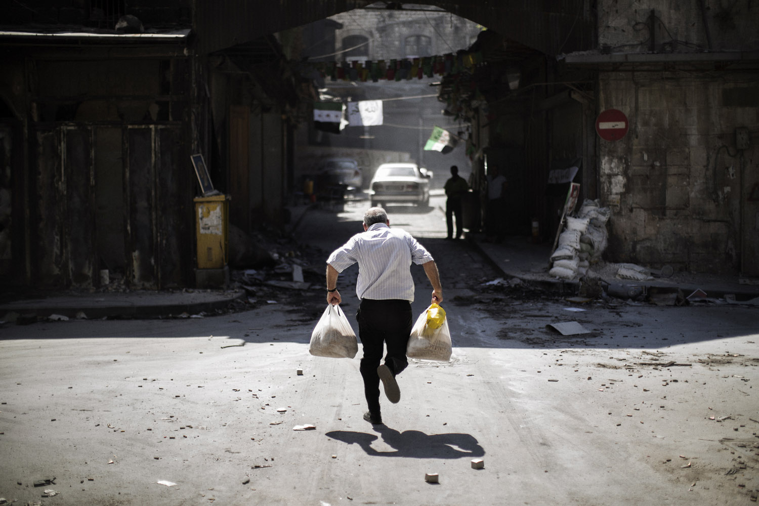 Sept. 14, 2012. A Syrian man carrying grocery bags tries to dodge sniper fire as he runs through an alley near a checkpoint manned by the Free Syria Army in the northern city of Aleppo.