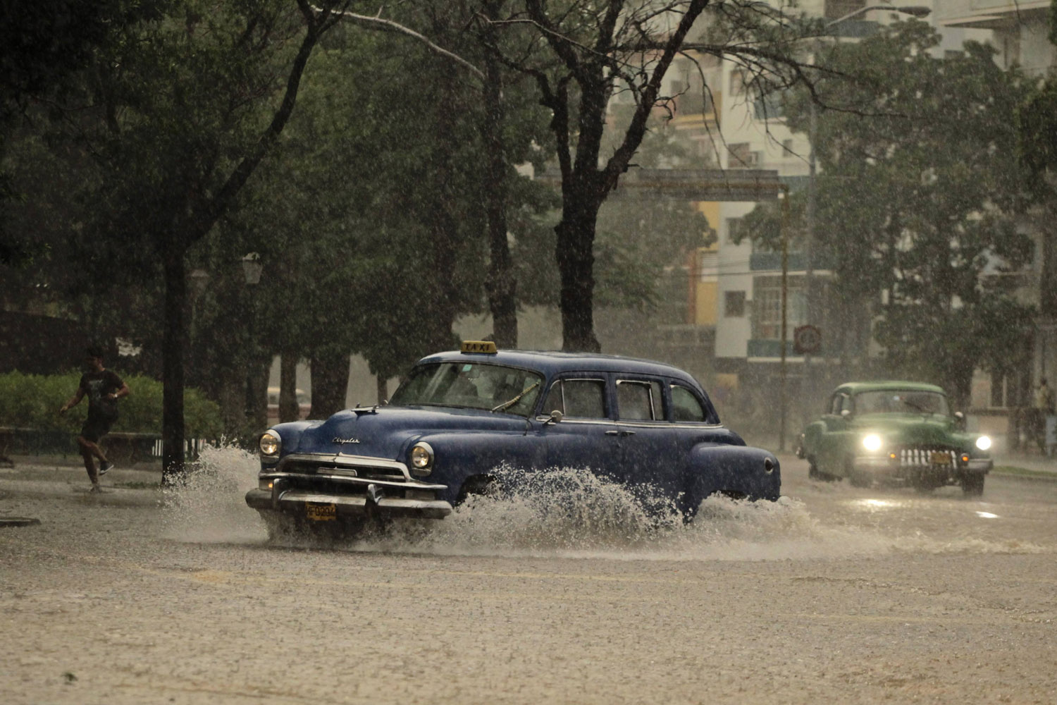 Sept. 15, 2012. Private licensed taxis are driven under heavy rain during a tropical thunderstorm in Havana.