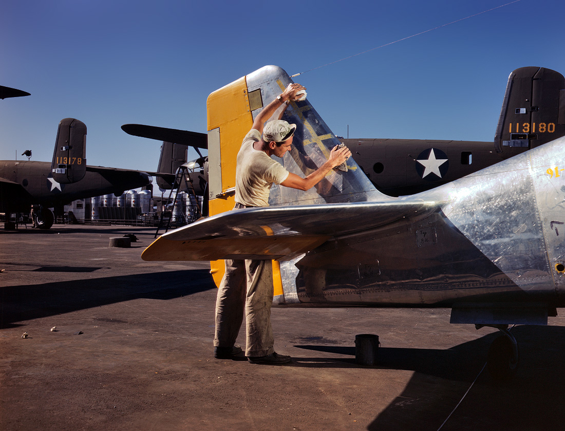 October 1942. A painter cleans the tail section of a P-51 Mustang fighter prior to spraying it with olive-drab camouflage. North American Aviation plant, Inglewood, Calif.