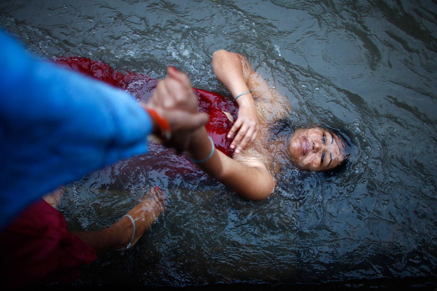 Sept. 20, 2012. A Nepalese devotee takes a holy dip with the help of a friend in the Bagmati River during Rishi Panchami, a purifying and atonement day for women, in Katmandu.