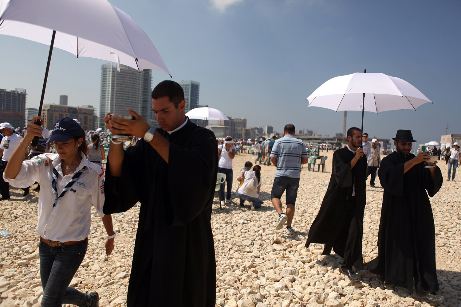 Sept. 16, 2012. Lebanese Catholic priests walk under umbrellas as they head towards the crowd to give the Eucharist during a mass led by Pope Benedict XVI at Beirut's waterfront.