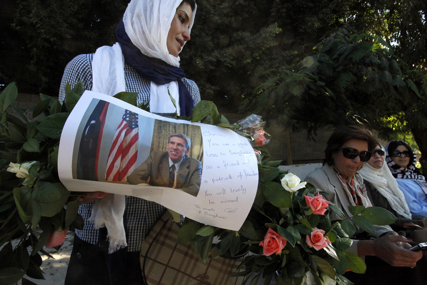 Sept. 17, 2012. A Libyan woman carries a wreath with a photo of U.S. Ambassador Chris Stevens on it as she and other Libyan and American women gather to pay their respect to the victims of the Sept. 11, 2012 attack on the U.S. consulate, in Benghazi, Libya.