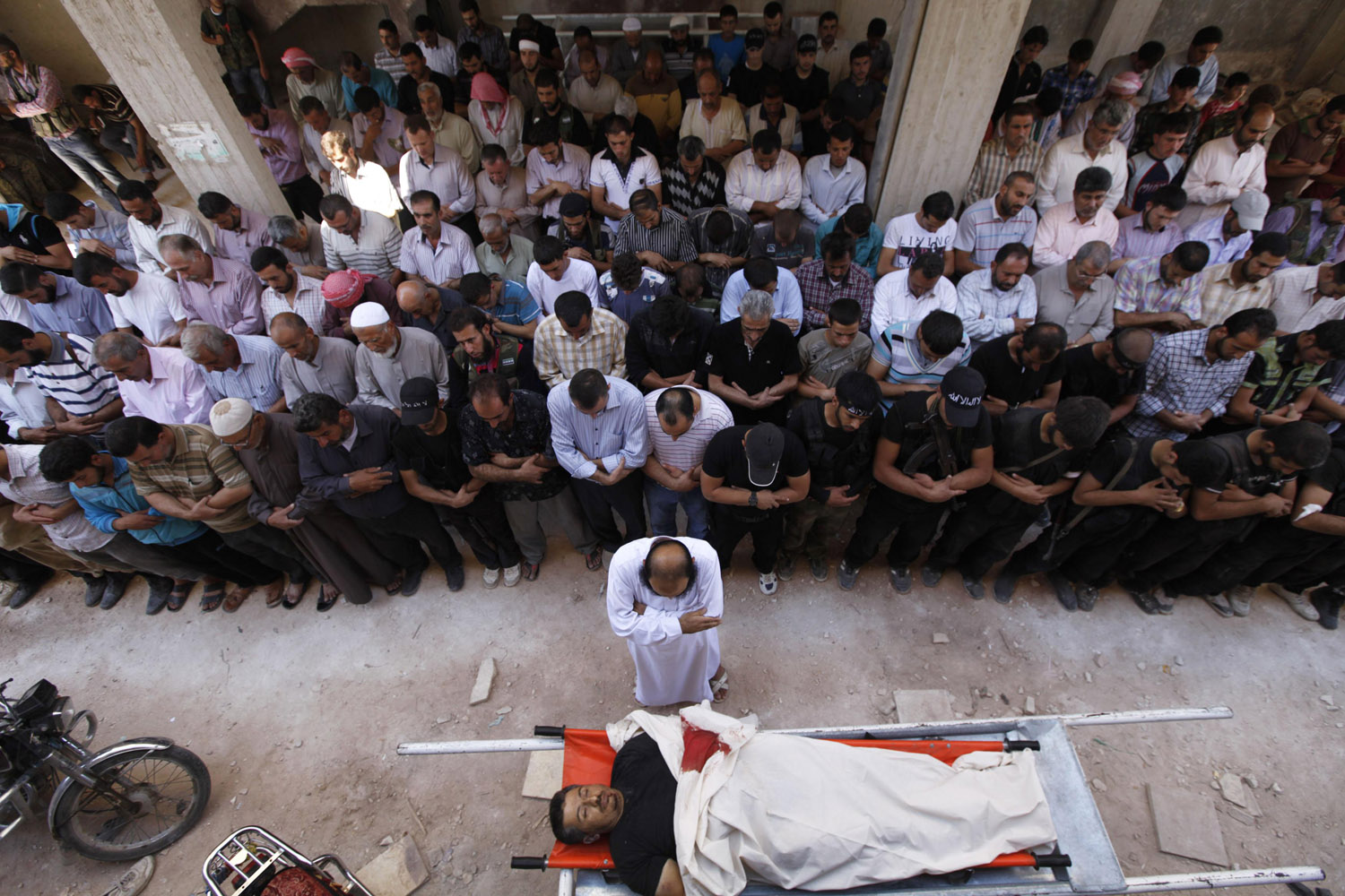 Sept. 17, 2012. Civilians and Islamist fighters pray over the body of Tareq Naser, an Islamist fighter who died during clashes, during his funeral near the village of Fafeen near Aleppo, Syria.