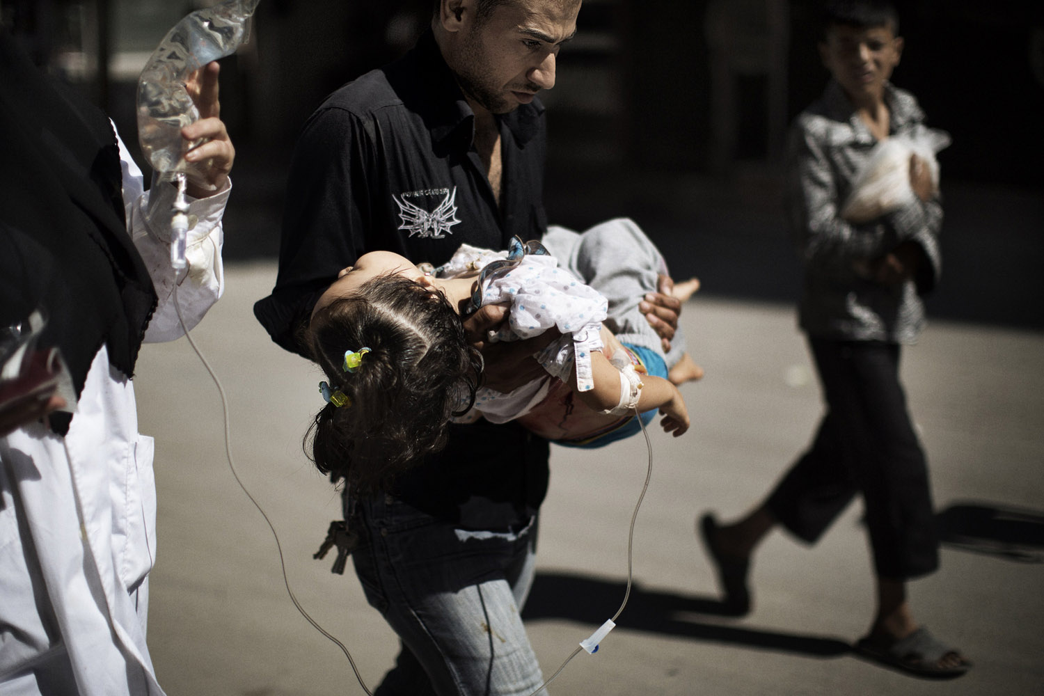 Sept. 18, 2012. A Syrian man carries his wounded daughter outside a hospital in the northern city of Aleppo.
