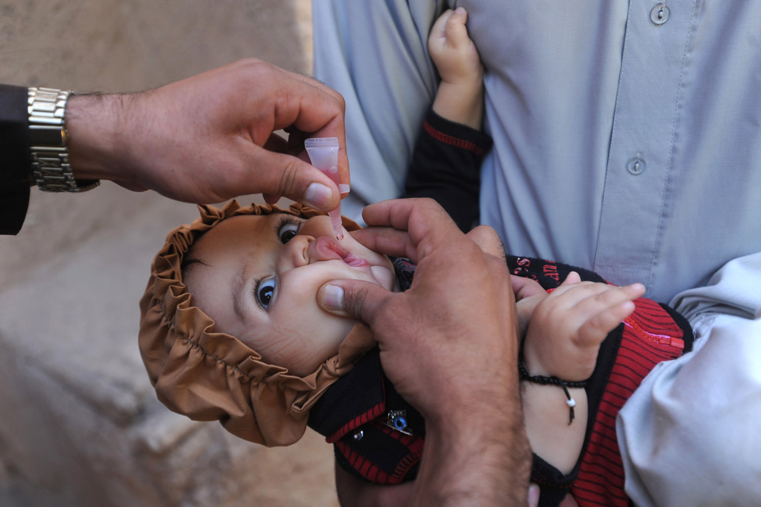 Sept. 18, 2012. An Afghan health worker administers a polio vaccination to a child on the third day of a vaccination campaign in Herat.
