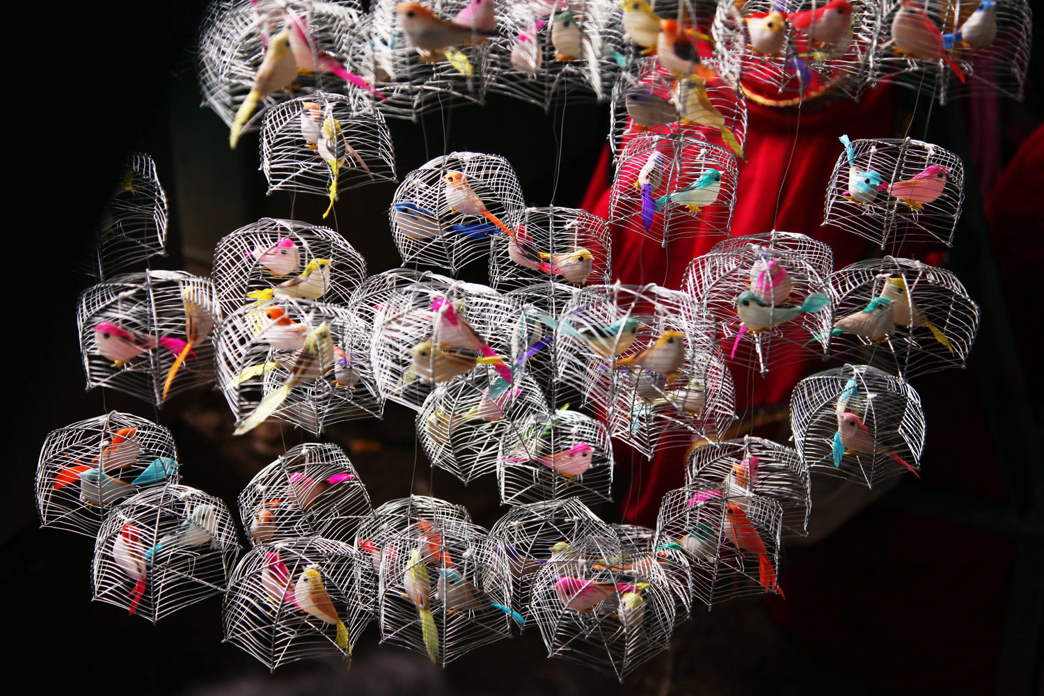 Sept. 18, 2012. Decorative toy birds are pictured as a vendor takes cover from the rains in New Delhi.