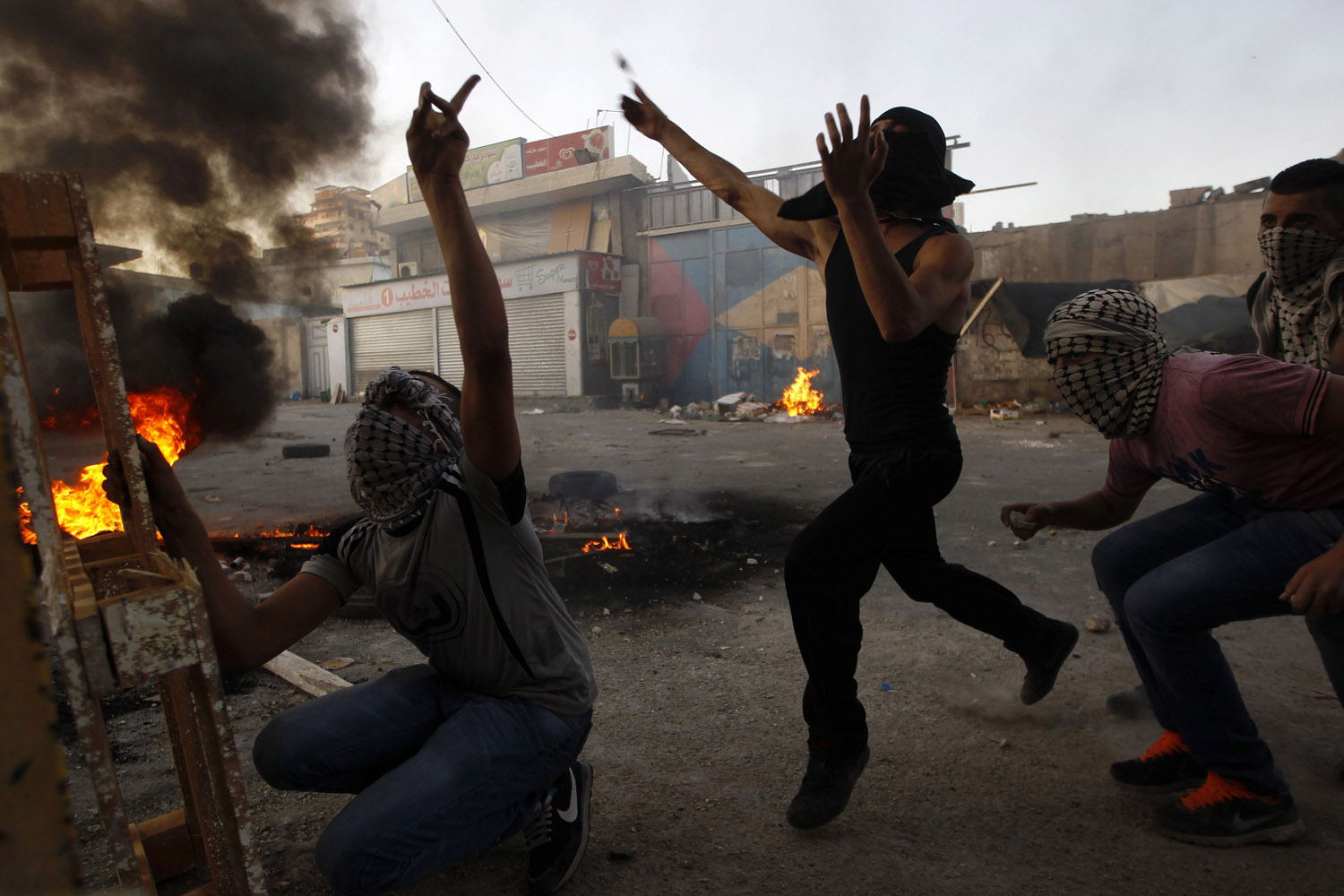 Sept. 18, 2012. Palestinian youths throw stones at Israeli border police (not seen)  in the Shuafat refugee camp in the West Bank near Jerusalem.