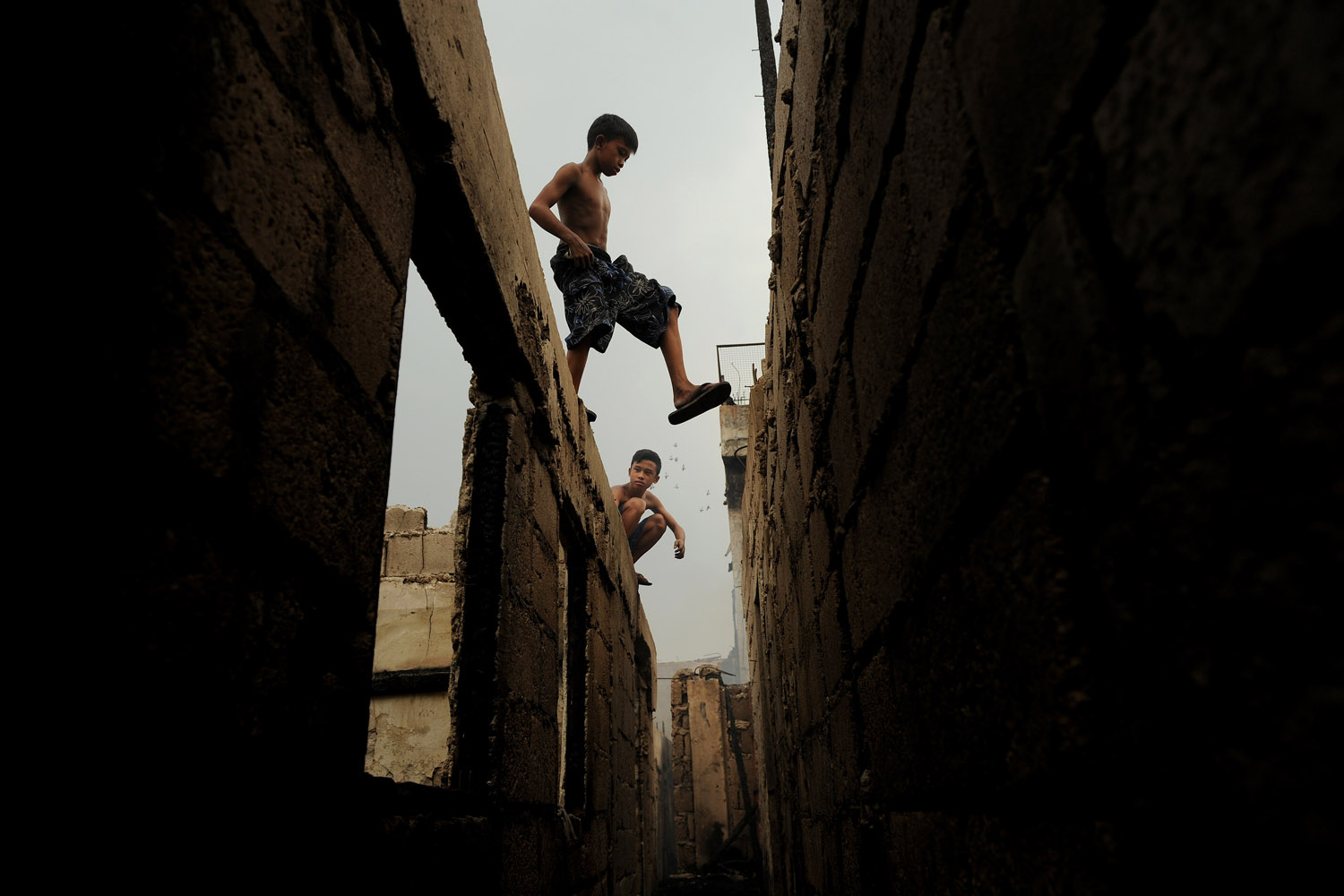 Sept. 19, 2012. Children walk above destroyed houses after a pre-dawn fire engulfed a slum area in Manila.