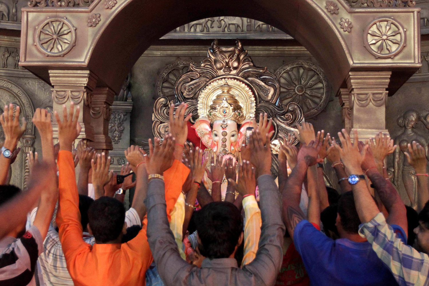 Sept. 19, 2012. Indian devotees raise their hands as they pray in front of an idol of the elephant-headed Hindu God Ganesha in Ahmadabad, India.