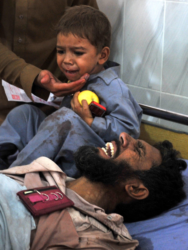 Sept. 19, 2012. A Pakistani child cries to his injured father at a hospital following a bomb explosion in Peshawar.