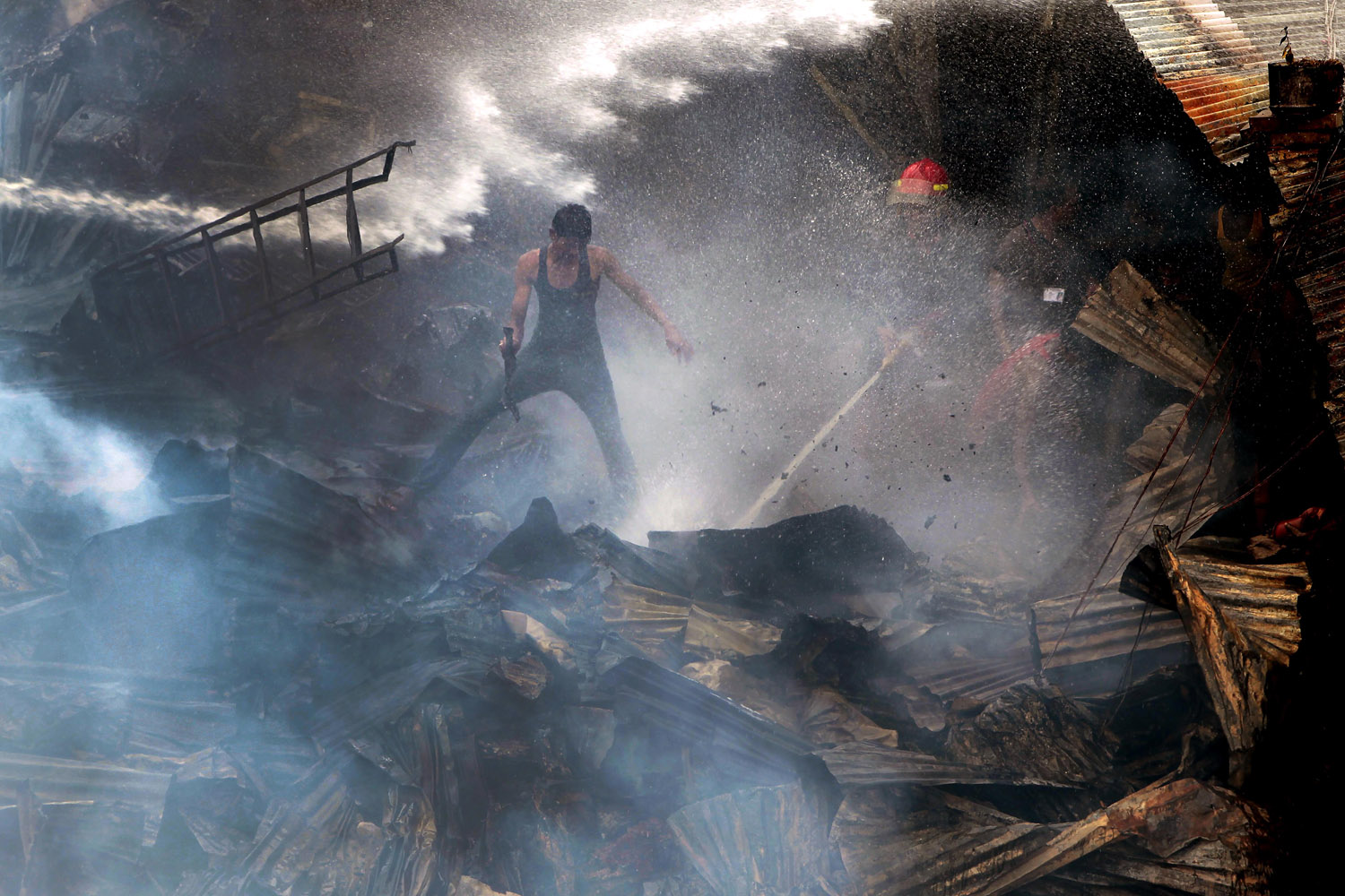 Sept. 20, 2012. Bangladeshi firefighters and residents try to control a fire in the Begunbari slum in Dhaka, Bangladesh.