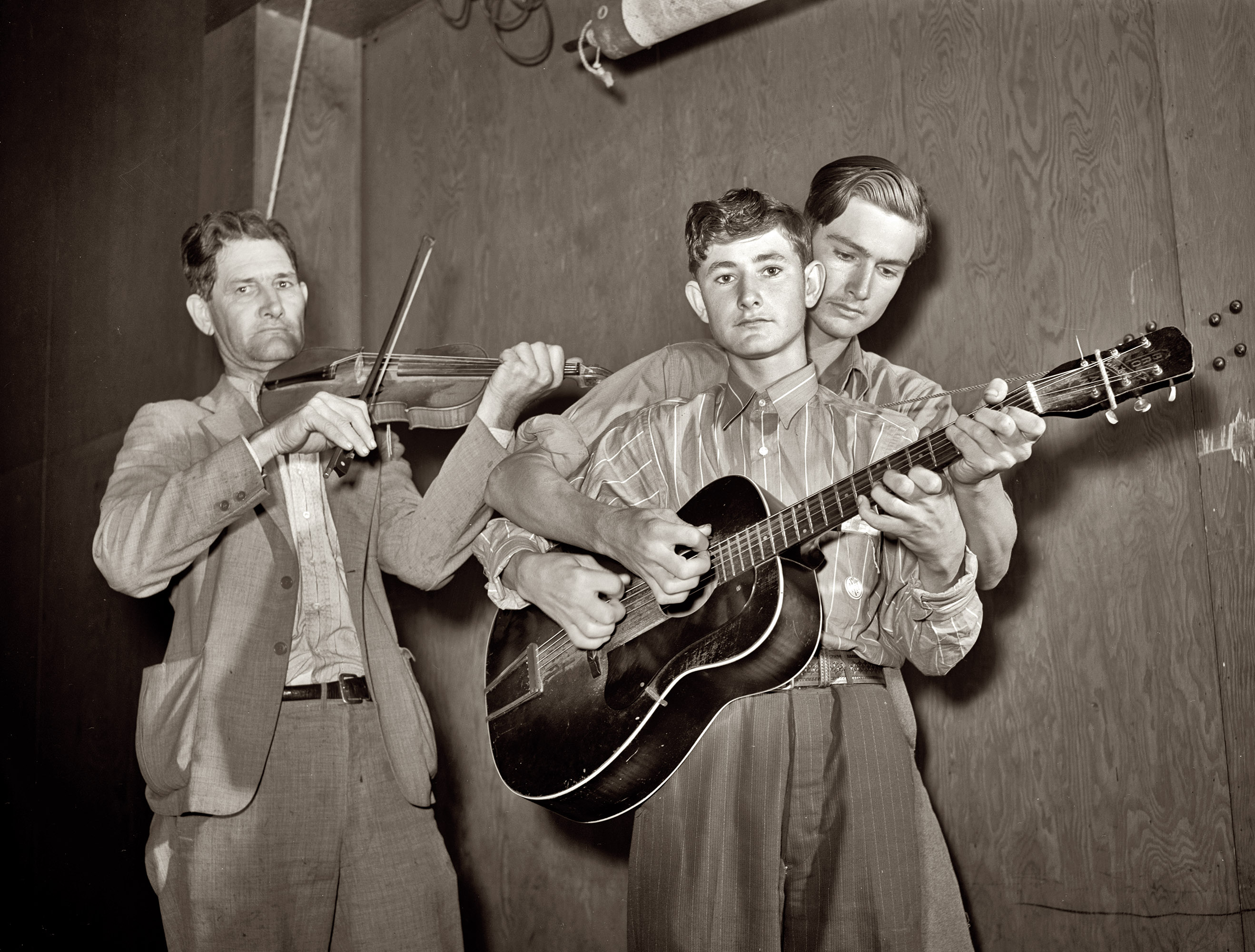 Weslaco, Texas. The  musical Drake family,  performing at a barn dance in the Farm Security Administration's Mercer G. Evans camp, February 1942. The fiddler is Nathan Drake, the younger boy is Jasper  Sleepy  Drake, and behind him is brother Weldon Drake.