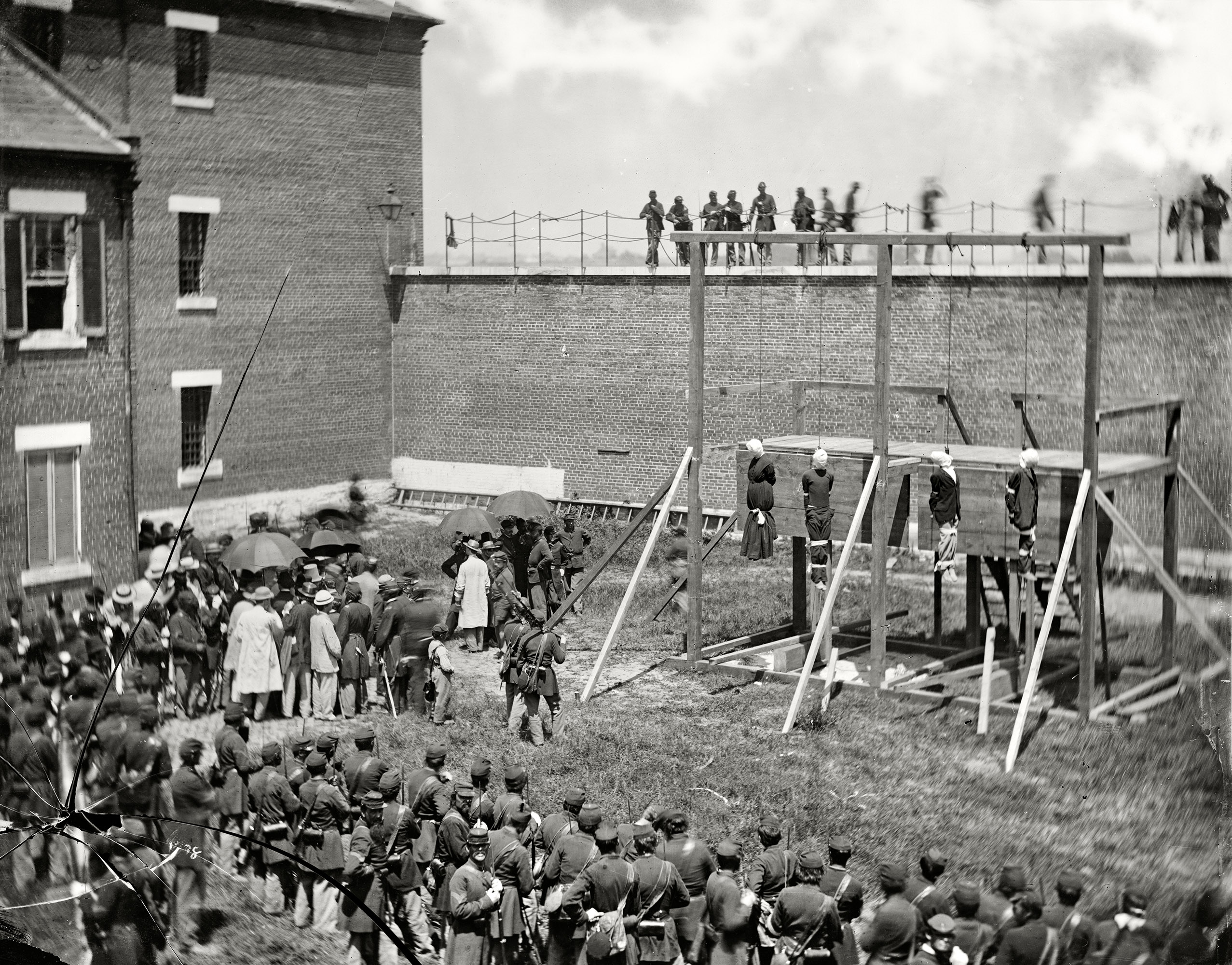 July 7, 1865.  Washington, D.C. Hanging hooded bodies of the four conspirators; crowd departing.  Lincoln assassination conspirators Mary Surratt, Lewis Payne, David Herold and George Atzerodt shortly after their execution at Fort McNair.