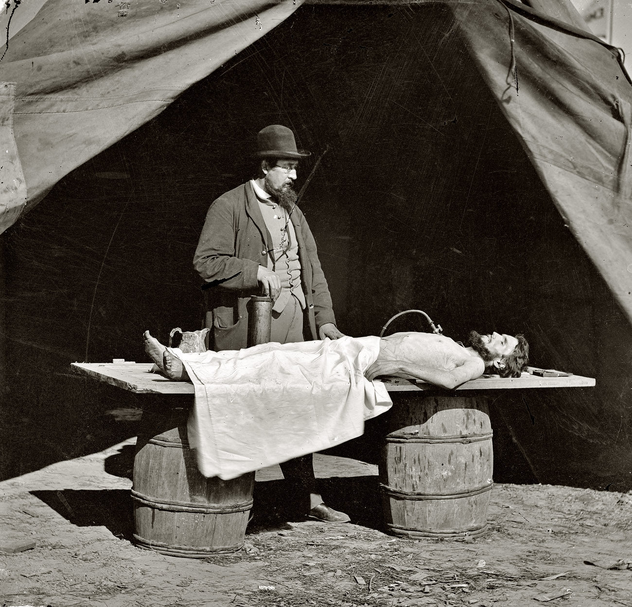 Circa 1861-1865.  Unknown location. Embalming surgeon at work on soldier's body. From photographs of artillery, place and date unknown.