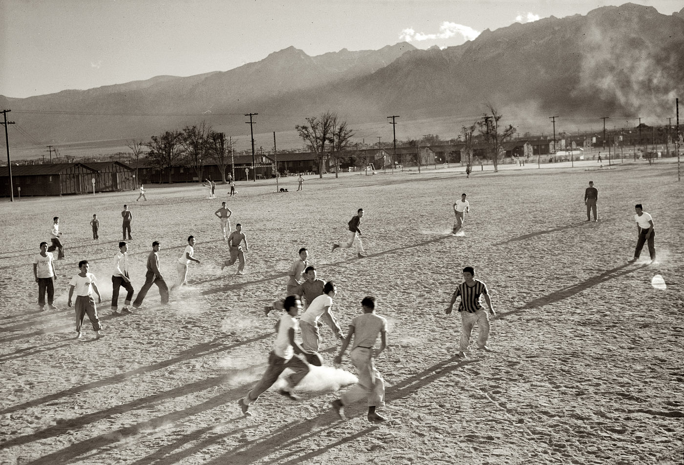 1943. Japanese-American internees at the Manzanar War Relocation Center in California.  Players involved in a football game on a dusty field, buildings and mountains in the distance.