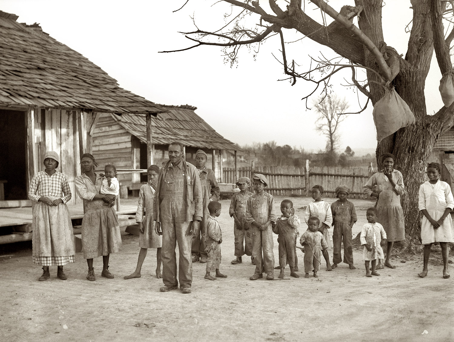 February 1937. Gee's Bend, Alabama. Descendants of former slaves of the Pettway Plantation. They are still living under primitive conditions there. Meat in sacks hangs from tree limbs to be cured.