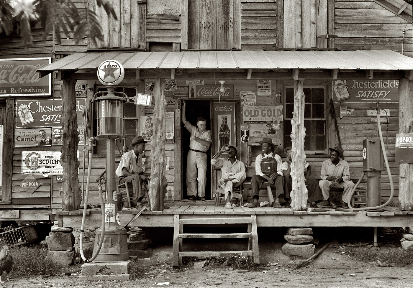 July 1939. Gordonton, North Carolina.  Country store on dirt road. Sunday afternoon. Note kerosene pump on the right and the gasoline pump on the left. Rough, unfinished timber posts have been used as supports for porch roof. Negro men sitting on the porch. Brother of store owner stands in doorway.