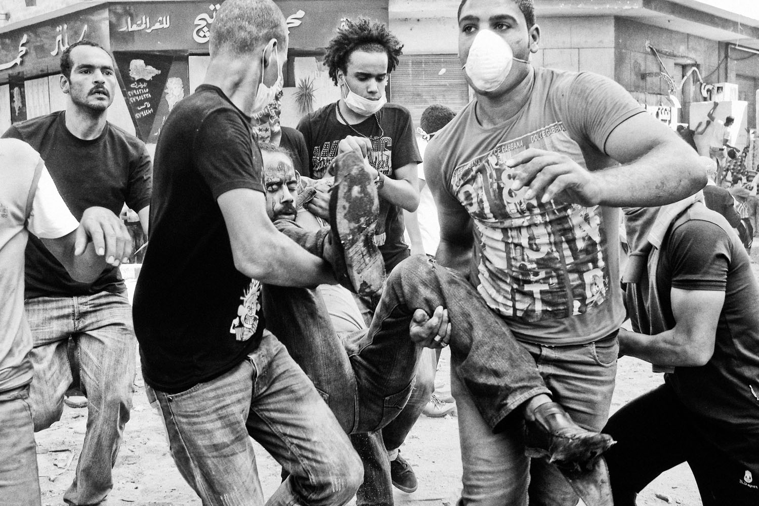 Protestors carry an injured comrade away from the scene.