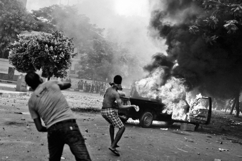 Protestors throw rocks at police near a burning vehicle.