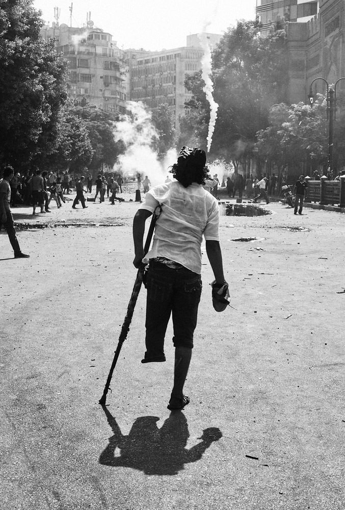 A protestor missing part of his leg stands watches the clashes near the U.S. Embassy.