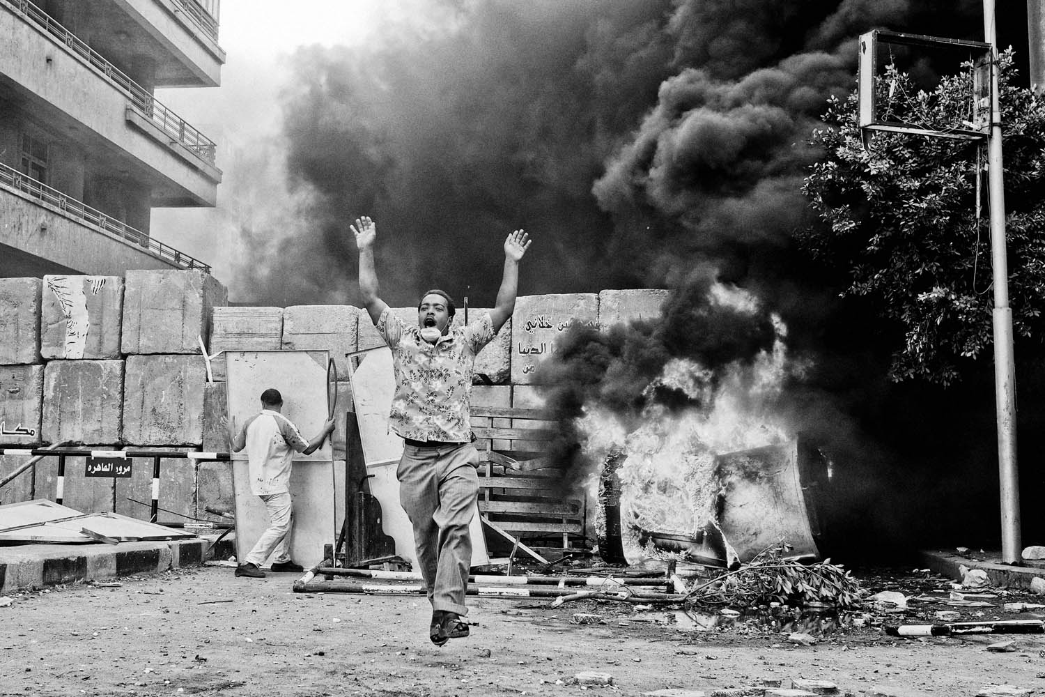 A protestor raises his arms in jubilation.