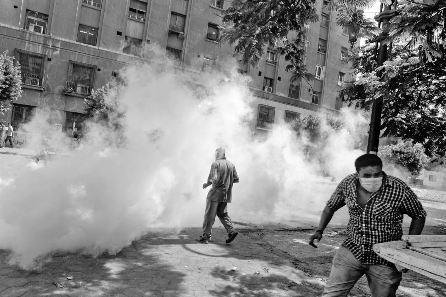 Protestors run away after a tear gas canister landed nearby.