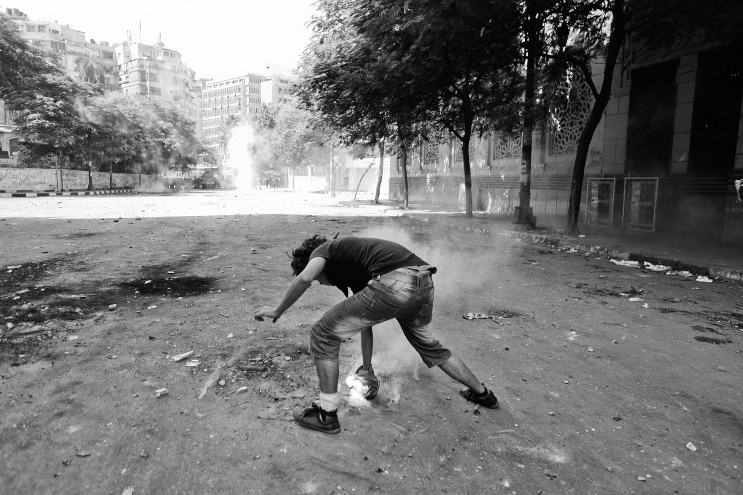 A protestor picks up a tear gas canister.