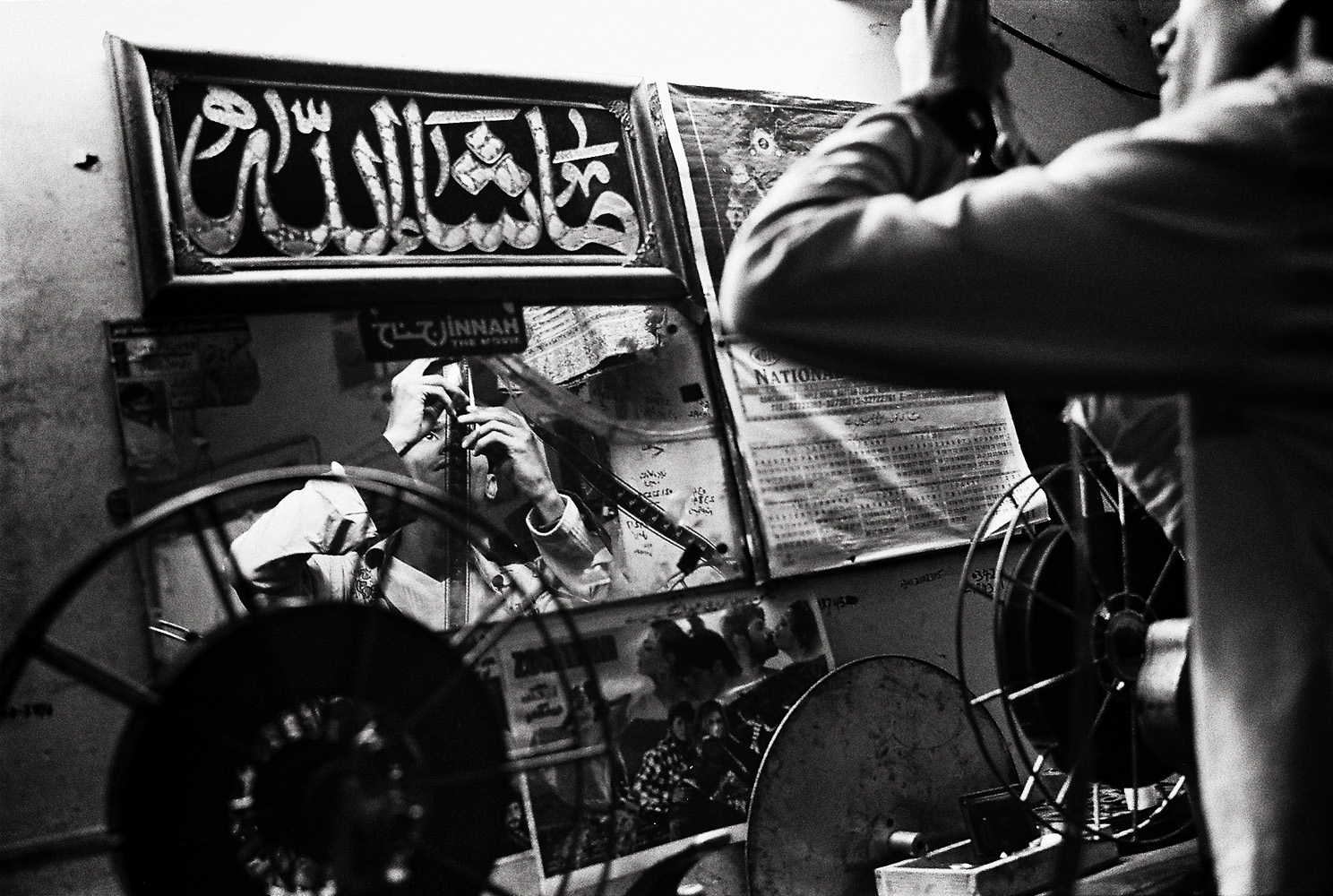 A Sindhi projectionist at Pashtun Cinema checks film before he threads it through the projector.  It's just a job. I couldn't care less about these films. They are all the same, anyway, dancing and guns.