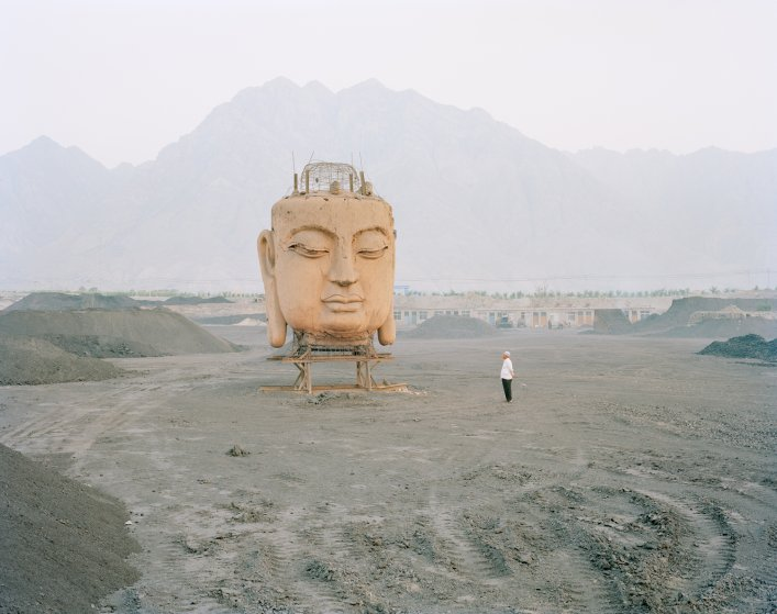 image: A giant Buddha's face in a coal yard, Ningxia province.