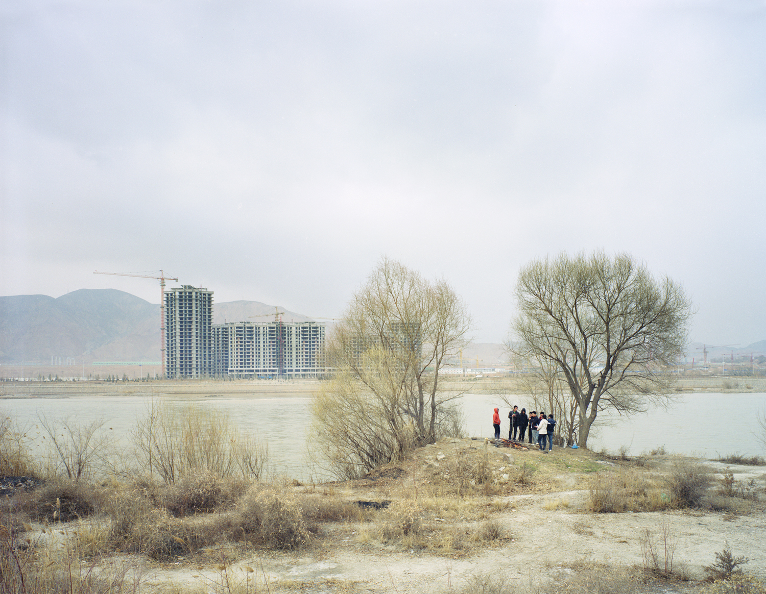 Young people gathered around a fire by the river, Gansu province.