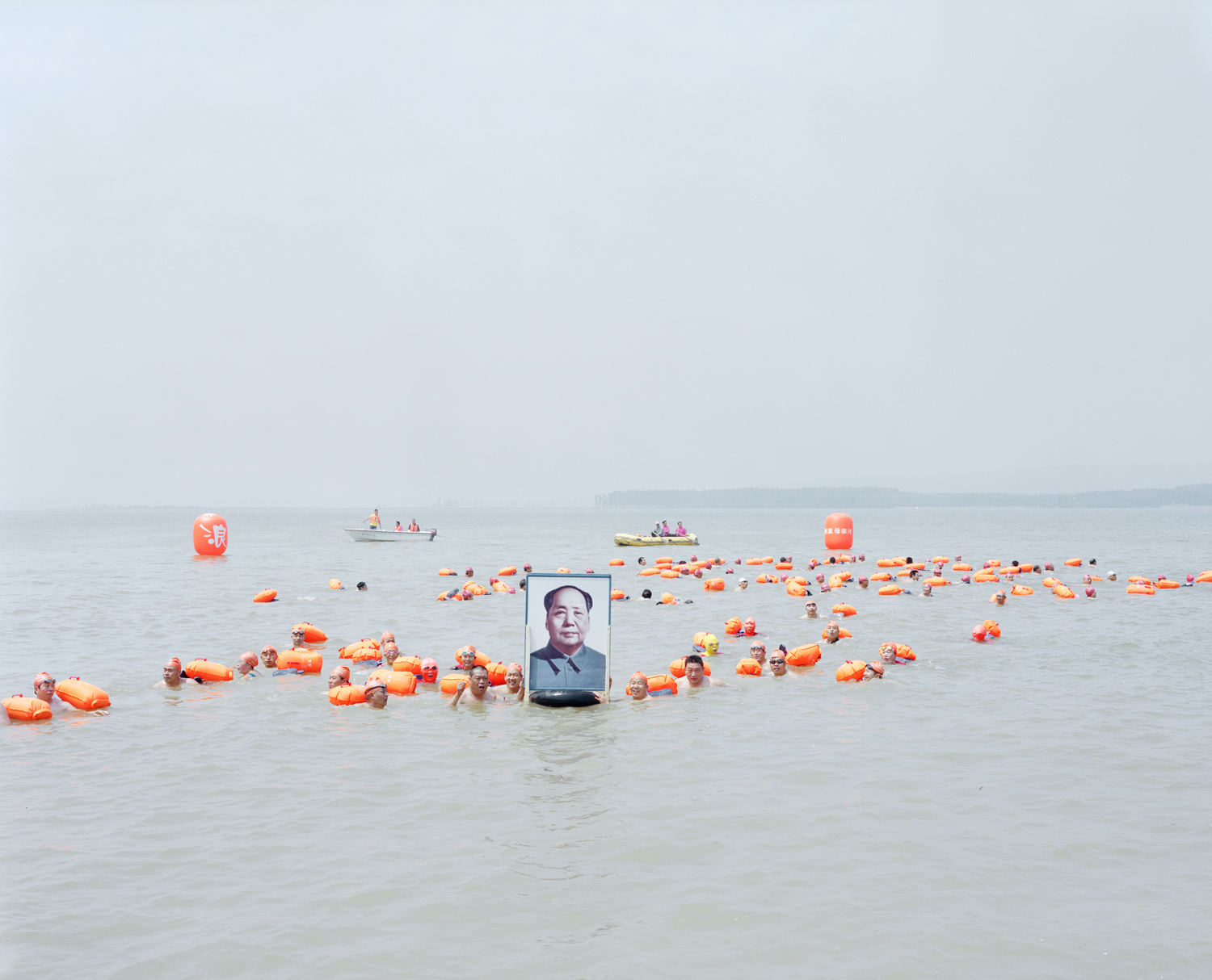 Locals hold a portrait of Mao as they swim across the river, Henan province.