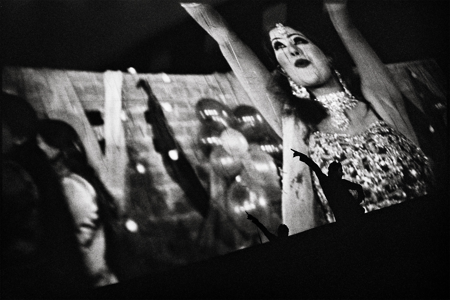 A Pashtun man dances on stage along to the musical number behind him on the screen. He is cheered on by the crowd.