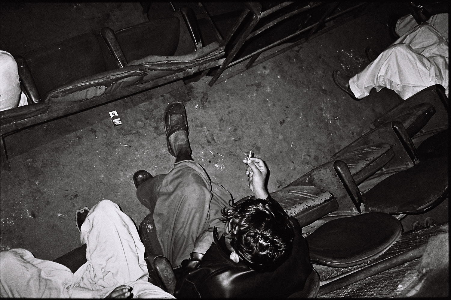 A young man idles in the back row of the movie theater, littering the floor with cigarette butts as he watches the film.