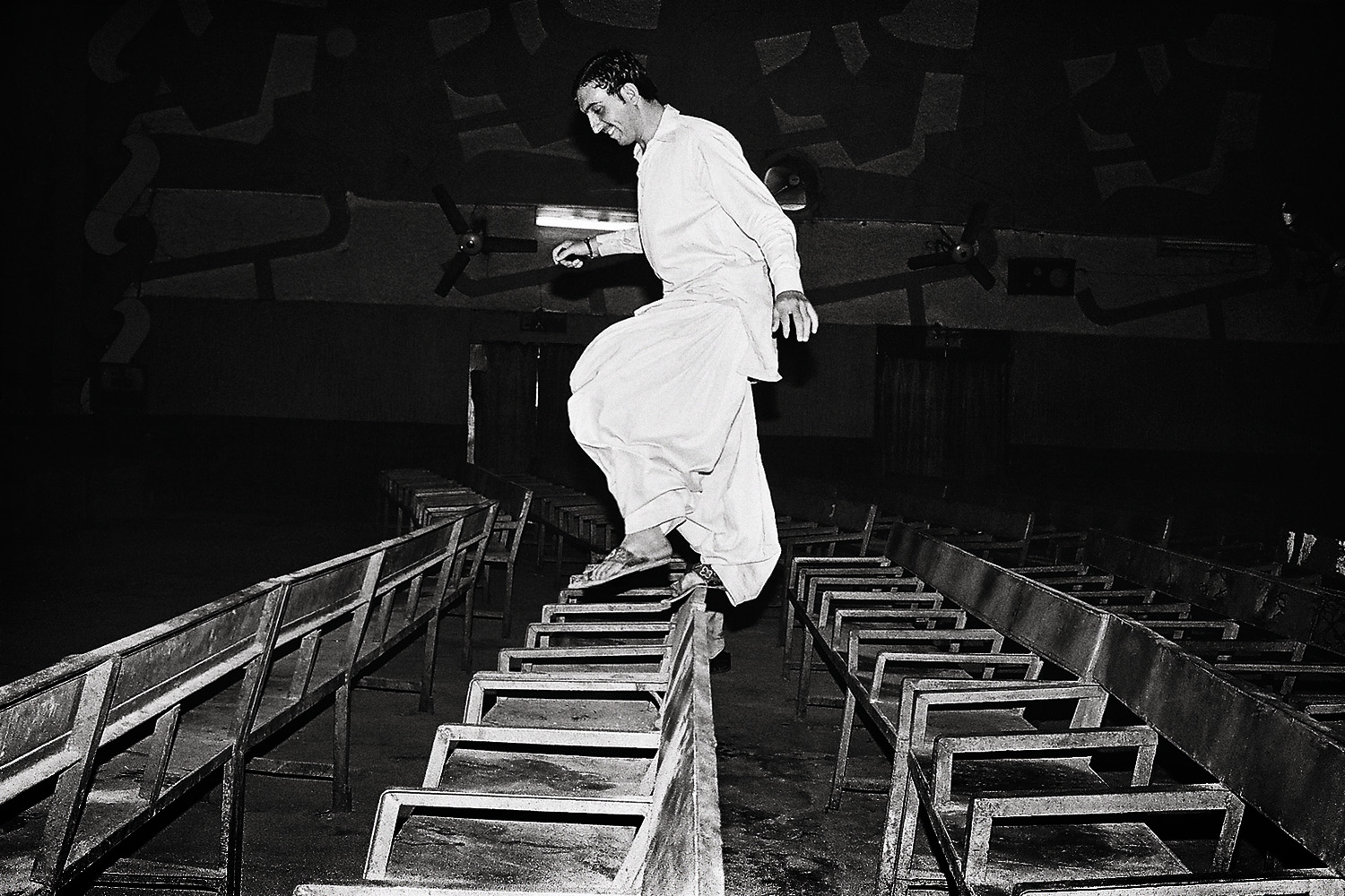 As the film ends and the crowds have cleared out, a young man exits by hopping over the seats.