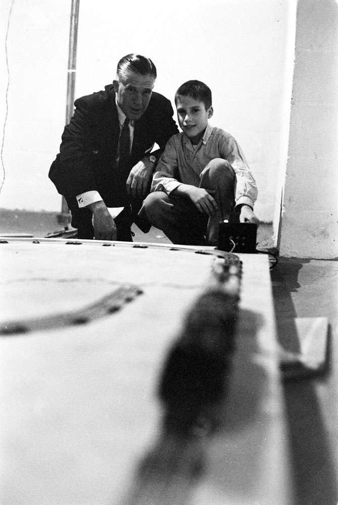 George Romney with his son, Mitt, playing with electric trains, 1958.