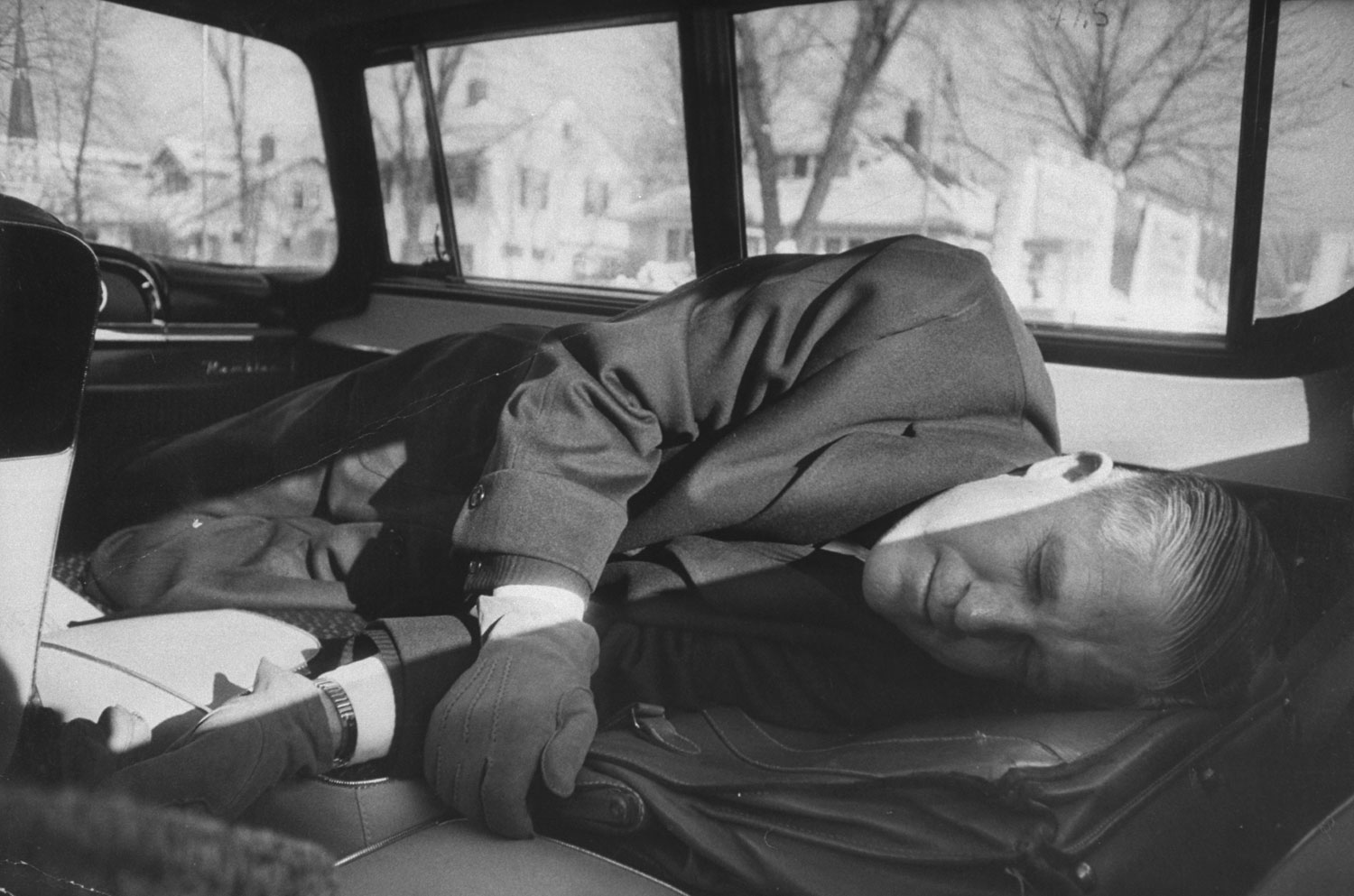 <b>Caption from LIFE.</b> From airport to Milwaukee [auto] body plant Romney takes catnap in Rambler station wagon built-in bed, with briefcase as pillow.
