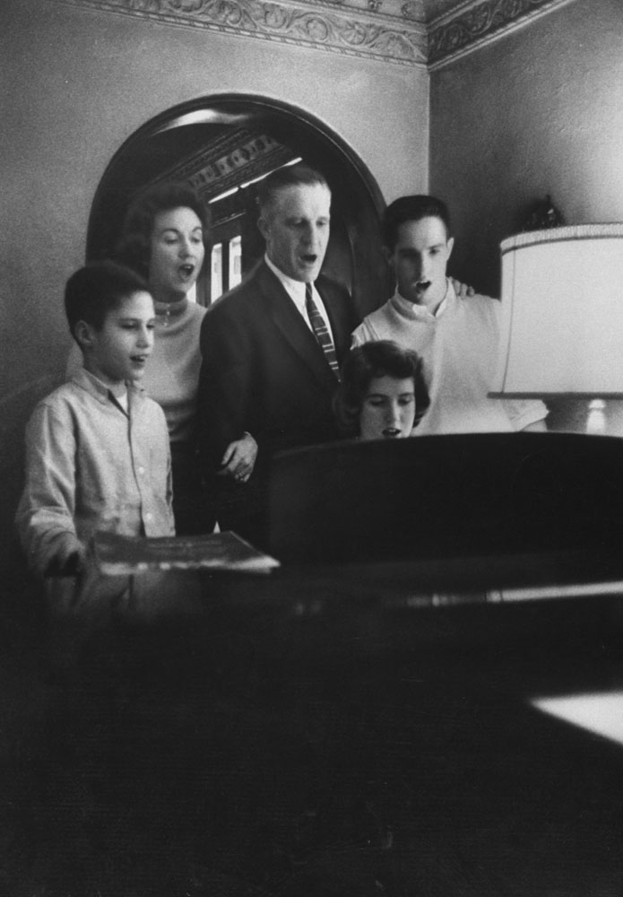 """<b>Caption from LIFE.</b> Romney family: Mitt, wife Lenore, son Scott, 16, and daughter Jane, 19, at piano, join together in a hymn. 'The biggest sale I ever made,' Romney said, 'was convincing Lenore to marry me. During our courtship she was offered $50,000 by Paramount to sign a five-year movie contract."""""""
