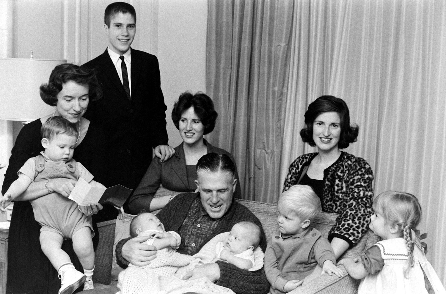 <b>Caption from LIFE.</b> After Sunday services the Romneys crowd onto a sofa in living room. Son Mitt and married daughters Jane and Lynn are at the rear. From left, grandchildren are Gregory (held by Lenore), Douglas, Susan, Brett and Jody. Another son, Scott, is in England with a mission group.