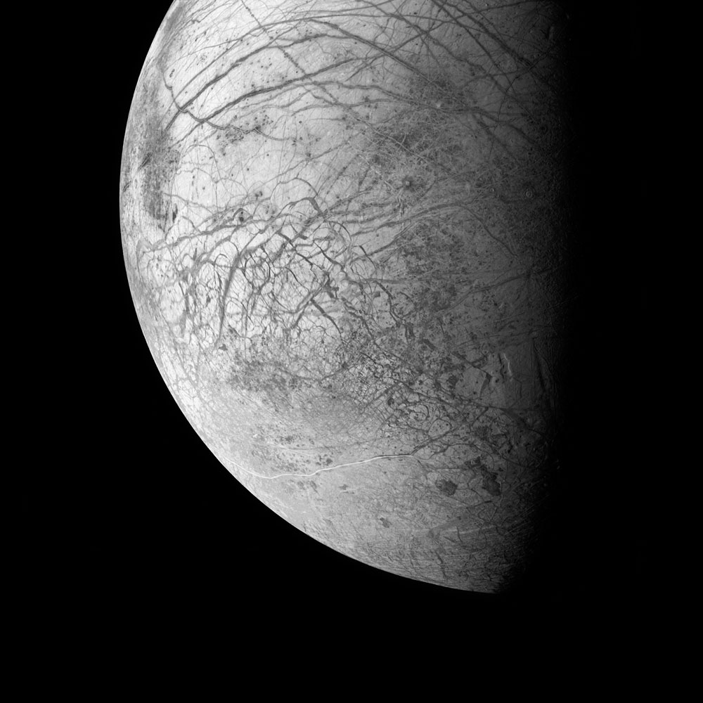 Chaos terrain, faults, and curving ridges cover the face of Europa, one of the most tantalizingly enigmatic worlds in the Solar System. Europa almost certainly has a vast, ice-capped global ocean kept warm by the gravitational effects of Jupiter and its moons, and perhaps by volcanoes on the sea floor. Europa may have enough heat, water, and organic material for life to have evolved here.                               Galileo, March 29, 1998