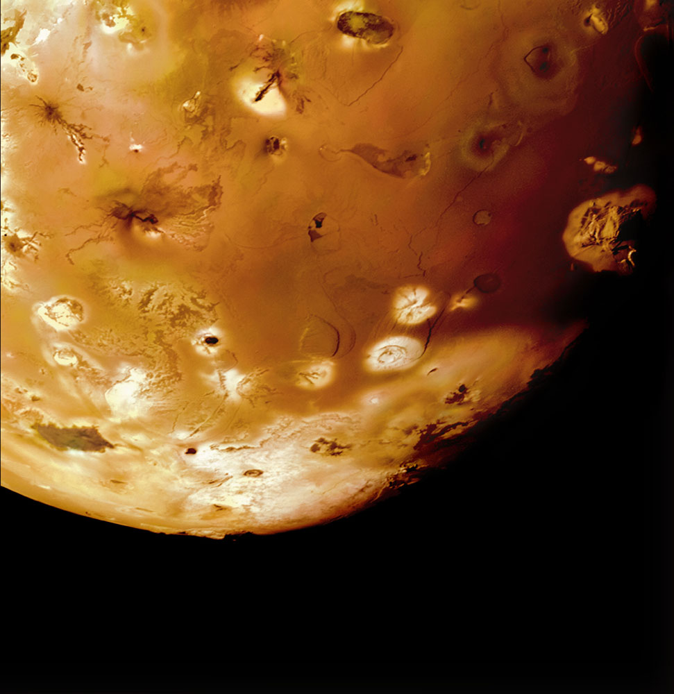 Io's volcanic plains with Haemus Montes, a 6-mile-high mountain, at the day-night terminator to the right.                               Multi-frame mosaic.                               Voyager 1, March 5, 1979